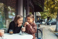Barn som har gyckel i utomhus- kafé Royaltyfri Foto