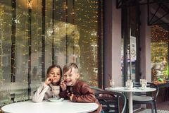 Barn som har gyckel i utomhus- kafé Arkivbilder