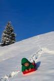 Barn som har gyckel i vinter, på en släde Arkivbilder