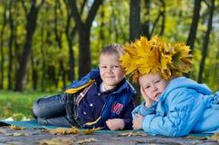 Barn som har gyckel med fallleaves Arkivbilder