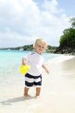 Barn som har gyckel på den tropiska stranden nära havet Arkivbild