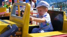 Barn som har gyckel på ett nöjesfält Rida bilen Arkivbild