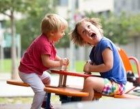 Barn som har gyckel på lekplatsen Royaltyfri Fotografi