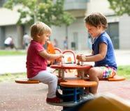 Barn som har gyckel på lekplatsen Arkivbild