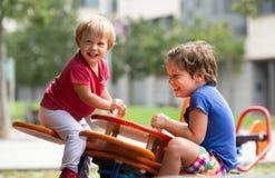 Barn som har gyckel på lekplatsen Royaltyfri Foto
