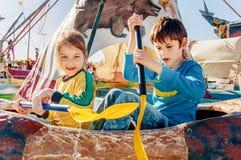 Barn som har gyckel på nöjesfältet Ritt på kanoten lyckligt barndombegrepp arkivfoto