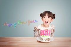 Barn som har gyckel på partiet för nytt år med kakan och stearinljuset 2017 Royaltyfri Foto