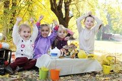 Barn som har gyckel på picknick på nedgången Arkivfoto