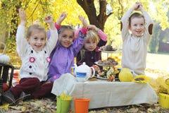 Barn som har gyckel på picknick på nedgången Arkivbild