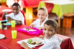 Barn som har lunch under avbrottstid i skolakafeteria royaltyfria bilder