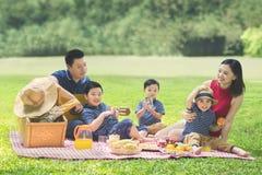 Barn som har picknick med deras föräldrar i parkera Royaltyfria Bilder