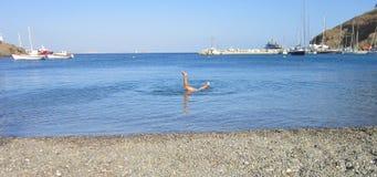 Barn som har roligt och gör trick i vattnet Fotografering för Bildbyråer