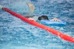 Barn som har simningkurs i simbassängen Royaltyfri Bild