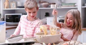Barn som har smutsig rolig bakning i kök arkivfilmer
