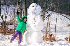 Barn som har vintergyckel nära en snögubbe Arkivbild
