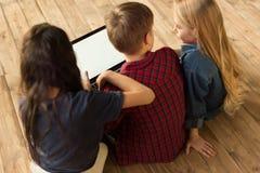 Barn som hemma använder den digitala bärbara datorn Royaltyfri Foto