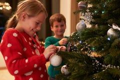 Barn som hemma dekorerar julgranen Royaltyfri Fotografi