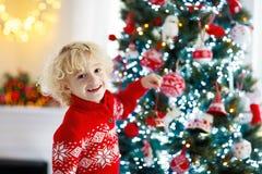 Barn som hemma dekorerar julgranen Pys i stucken tröja med Xmas-prydnaden Familjen med ungar firar vinter royaltyfri foto