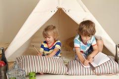 Barn som hemma spelar inomhus med ett tipitält Fotografering för Bildbyråer