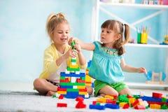Barn som hemma spelar på golvet med kuber royaltyfri bild