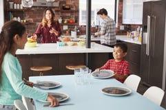 Barn som hjälper att lägga tabellen som är klar för familjmål royaltyfri bild