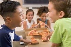 barn som inomhus äter fyra pizzabarn Arkivfoto