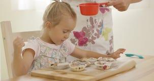 Barn som intresseras i socker som faller på bakade muffin royaltyfria bilder