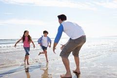 Barn som kör in mot fadern On Beach Fotografering för Bildbyråer