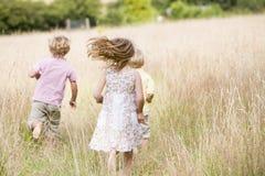 barn som kör utomhus tre barn Arkivbild