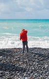 Barn som kastar en sten in i havet royaltyfria foton