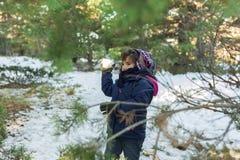 Barn som kastar snö, klumpa ihop sig i dettäckte berget royaltyfri bild
