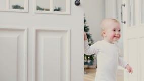 Barn som kikar ut ur den öppna rumdörren lager videofilmer