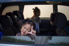 Barn som kopplar av i bil under v?gtur royaltyfri foto