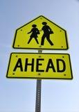 barn som korsar skolateckenvarning Arkivfoto