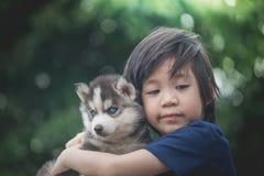 Barn som kramar den siberian skrovliga valpen royaltyfri bild