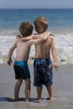 Barn som kramar på stranden. arkivfoto