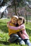 barn som kramar två Arkivbild