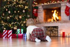Barn som kryper till gåvor som ligger under julgranen Arkivfoton