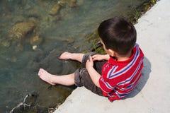 Barn som kyler fot i vatten Royaltyfria Foton