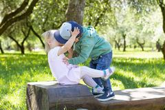 Barn som kysser i trädgården Arkivfoto
