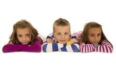 Barn som lägger, ner i lycklig pyjamas och att le Royaltyfria Foton
