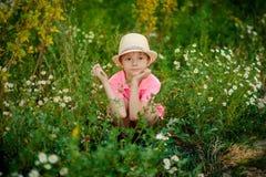Barn som lägger på gräset med tusenskönor Royaltyfria Foton