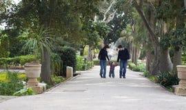 Barn som lär att gå med föräldrar Arkivfoton