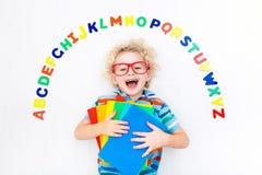 Barn som lär bokstäver av alfabetet och läsning fotografering för bildbyråer