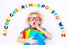 Barn som lär bokstäver av alfabetet och läsning Royaltyfri Foto