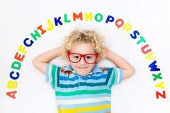 Barn som lär bokstäver av alfabetet och läsning Arkivfoton