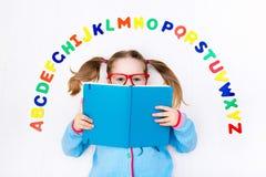 Barn som lär bokstäver av alfabetet och läsning Royaltyfri Bild