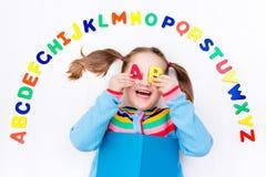 Barn som lär bokstäver av alfabetet och läsning Arkivfoto