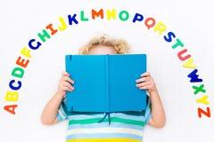 Barn som lär bokstäver av alfabetet och läsning Arkivbild