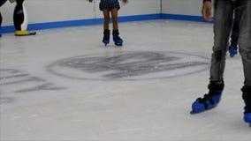 Barn som lär hur till isskridskon i en rekreationkorridor arkivfilmer